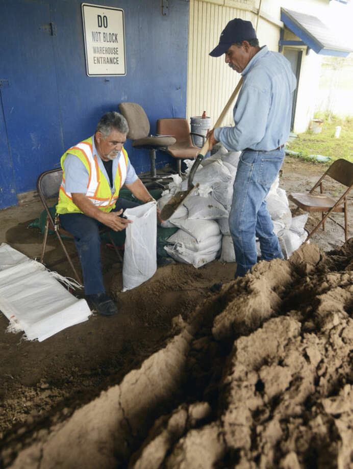 Cameron County Precinct 1 employees Chon Garcia and Rene Murillo begin filling sandbags at the Precinct 1 Warehouse, Friday, Oct. 23,2015, in Brownsville,Texas, in anticipation of flooding due to Hurricane Patricia. (Brad Doherty /The Brownsville Herald via AP) MANDATORY CREDIT