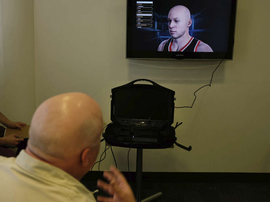 In this photo taken Tuesday, Sept. 16, 2014, 2K Sports Vice President Sports Development, Jeffrey Thomas, looks at a 3D model of his face build by his company, 2K Sports' 3D face-capturing technology, processed with the help of a stereoscopic camera attached to a Sony PS4 video console during a preview demonstration, in Los Angeles. The NBA 2k15 upcoming basketball simulation video game developed by Visual Concepts and published by 2K Sports releases Oct. 7, 2014. (AP Photo/Richard Vogel)
