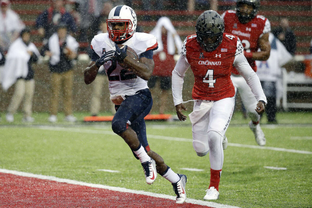 Connecticut running back Arkeel Newsome (22) runs in for a touchdown against Cincinnati safety Zach Edwards (4) in the first half of an NCAA college football game in the rain Saturday, Oct. 24, 2015, in Cincinnati. (AP Photo/John Minchillo)