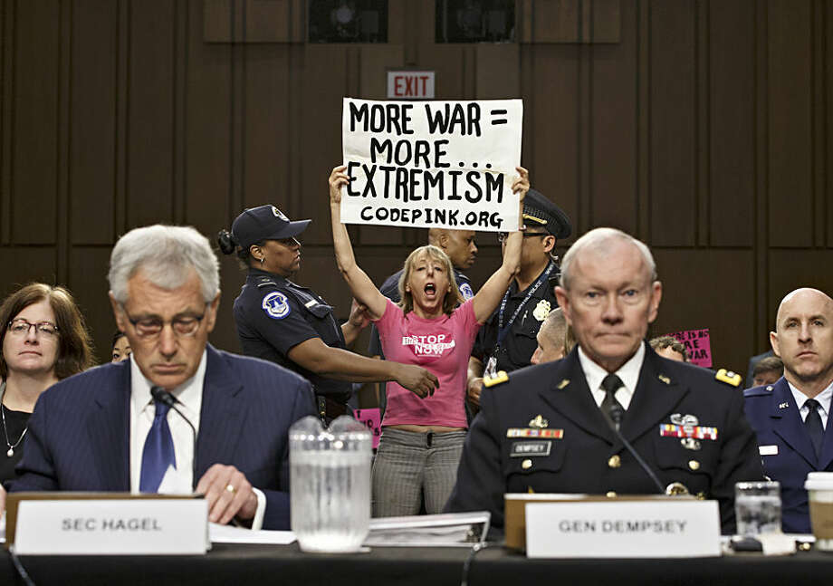 Members of the anti-war activist group CodePink interrupt a Senate Armed Services Committee hearing with Defense Secretary Chuck Hagel, left, and Army Gen. Martin Dempsey, chairman of the Joint Chiefs of Staff, on Capitol Hill in Washington, Tuesday, Sept. 16, 2014. It is the first in a series of high-profile hearings that will measure congressional support for President Barack Obama's strategy to combat Islamic State extremists in Iraq and Syria. (AP Photo/J. Scott Applewhite)