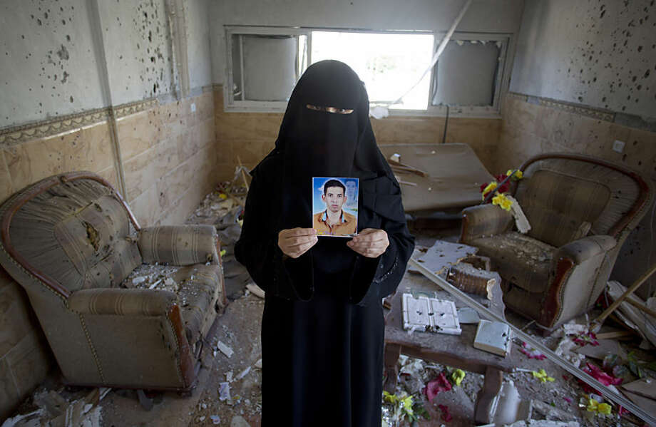 In this Tuesday, Sept. 16, 2014 photo, Palestinian Soad al-Jorf, 36, holds a photograph of her son Hussein al-Jorf, 19, in the living room of her house which was hit by Israeli shelling during the war in the town of Abasan, in the southern Gaza Strip. Desperate to flee Gaza after suffering through years of border closures and three wars, Hussein and his cousin Mohammed Abu Toaimeh, 22, paid traffickers to smuggle them to Europe. But the two cousins and dozens of other Gazans are missing amid reports that smugglers sunk their vessel on purpose. (AP Photo/Khalil Hamra)