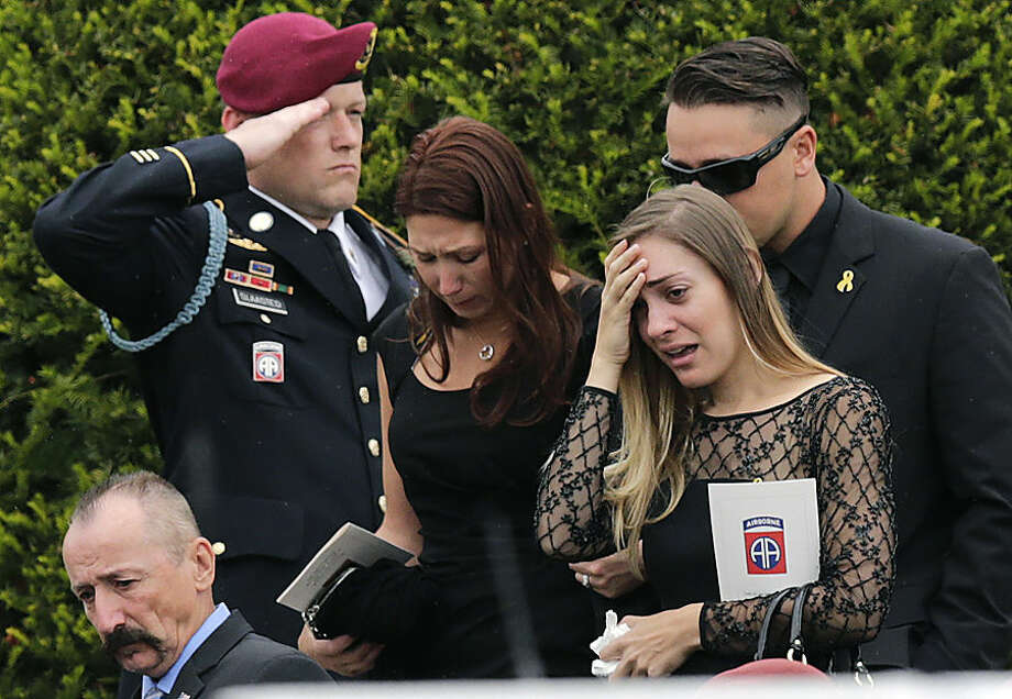Amanda Zullo, girlfriend of Army Spc. Brian Arsenault, holds her hand to her face as she follows his casket from the St. Rose of Lima Church during his funeral in Northborough, Mass., Tuesday, Sept. 16, 2014. Arsenault, a 28-year-old paratrooper with the 82nd Airborne Division, died earlier this month from injuries he suffered during a firefight between his unit and enemy forces in Afghanistan. (AP Photo/Charles Krupa)