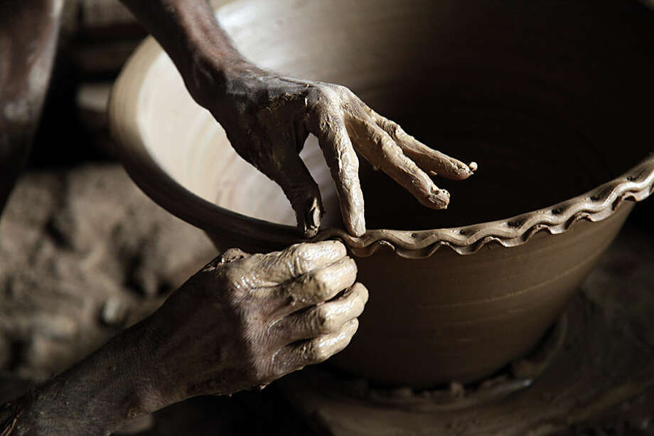 In this Aug. 29, 2014, photo, a man puts a decorative edge on a clay flower pot in Twante township, southwest of Yangon, Myanmar. For generations, the town has been known for its thriving pottery industry. But as Myanmar's economy has grown since opening it's doors to the outside world in 2011, the younger generation has been reluctant to learn the art of pottery. This, and the cost of transporting the bulky and fragile products, have turned it into an unstable, dying industry. (AP Photo/Khin Maung Win)