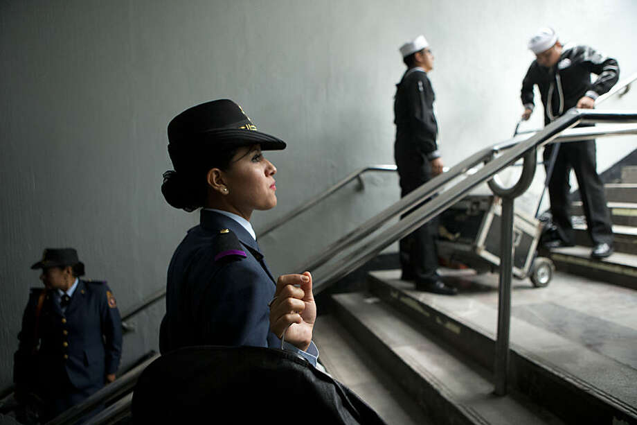 Members of the military gather their belongings from the stairwell of a closed subway entrance, as they leave following an Independence Day parade by Mexico's Armed Forces, in central Mexico City, Mexico, Tuesday, Sept. 16, 2014. Mexico is marking the 204th anniversary of its independence from Spain. (AP Photo/Rebecca Blackwell)