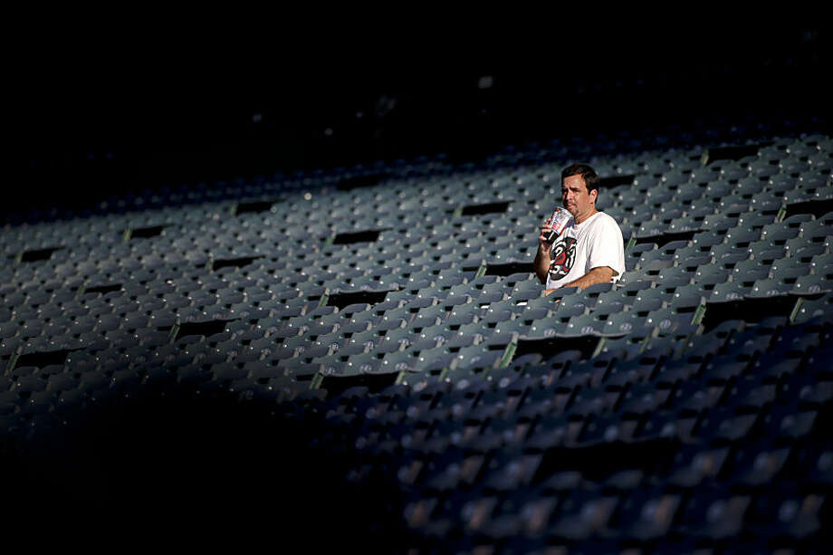 A lone fan drinks his soda while watching the Los Angeles Angels practice before a baseball game against the Seattle Mariners Monday, Sept. 15, 2014, in Anaheim, Calif. Southern California is roasting in triple-digit temperatures and forecasters say the heat wave will continue at least another day. (AP Photo/Jae C. Hong)