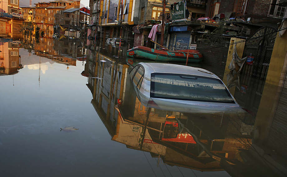 A car is partially submerged on a flooded street in Srinagar, Indian-controlled Kashmir, Monday, Sept. 15, 2014. Flooding from days of heavy monsoon rains partially submerged Srinagar and left more than 400 people dead in northern Pakistan and India. The flood waters have begun to recede, but vast fields of crops have been destroyed and tens of thousands of families have lost all their possessions. (AP Photo/Altaf Qadri)