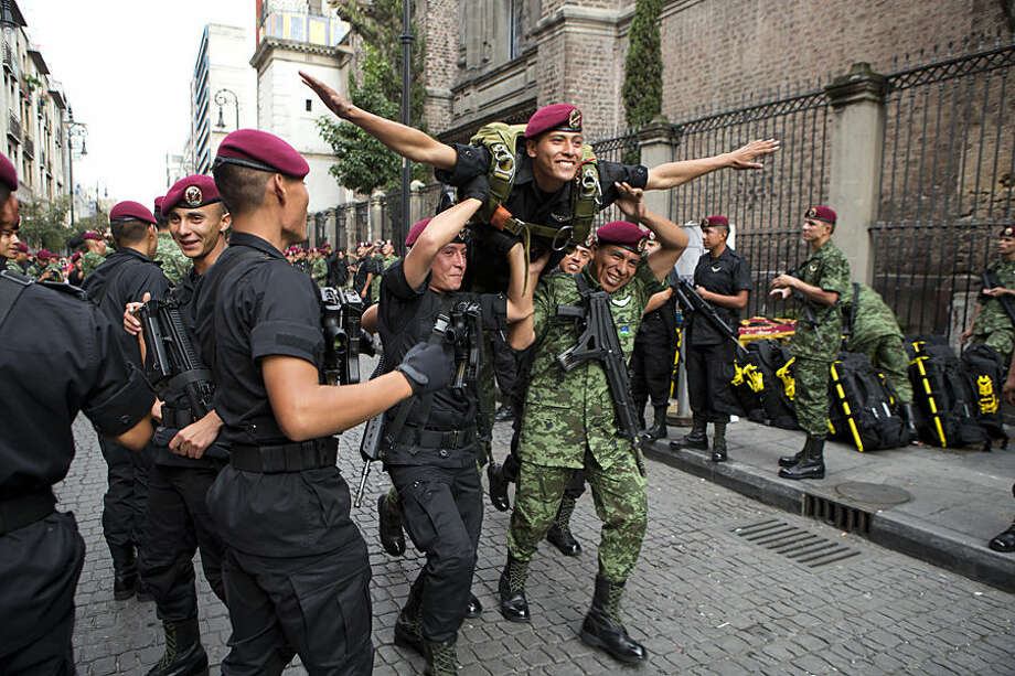 Members of a parachutist group run carrying a soldier, as they joke around ahead of the start of the Independence Day parade by Mexico's Armed Forces, in central Mexico City, Mexico, Tuesday, Sept. 16, 2014. Mexico is marking the 204th anniversary of its independence from Spain. (AP Photo/Rebecca Blackwell)
