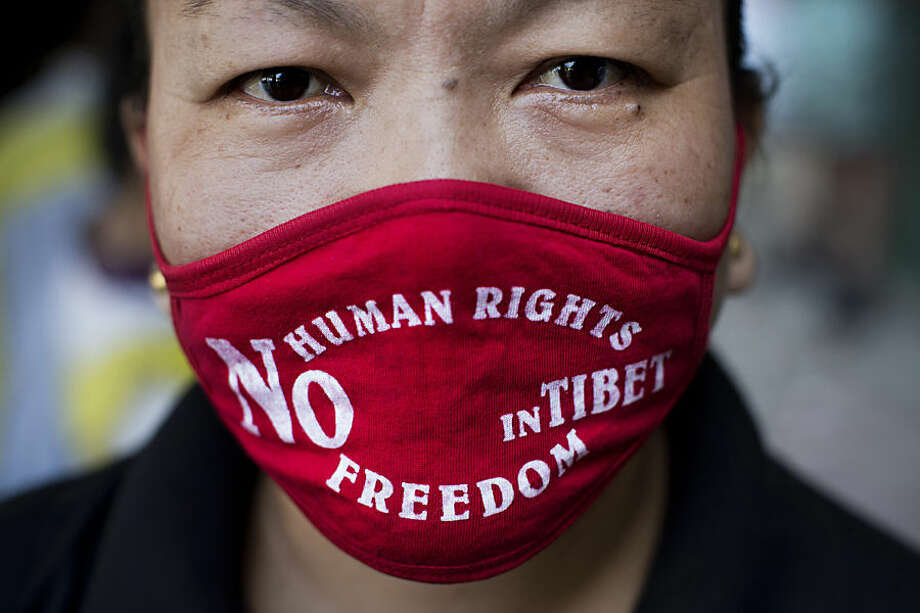 An Exile Tibetan woman wears a mask during a protest to highlight Chinese control over Tibet, coinciding with the visit of Chinese President Xi Jinping in New Delhi, India, Wednesday, Sept. 17, 2014. Xi was traveling Wednesday to India, where he and Prime Minister Narendra Modi are expected to discuss trade, infrastructure and territorial disputes. (AP Photo/Bernat Armangue)