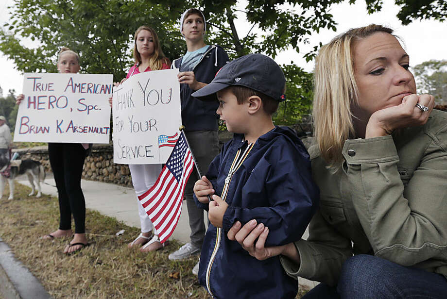 Jackson Gargalianos, 3, of Southborough, Mass., holds a flag as he stands with his mother, Cheri, as the funeral procession of Army Spc. Brian Arsenault, of the 82nd Airborne Division, passes in Northborough, Mass., Tuesday, Sept. 16, 2014. The 28-year-old Arsenault died earlier this month from injuries he suffered during a firefight between his unit and enemy forces in Afghanistan. (AP Photo/Charles Krupa)