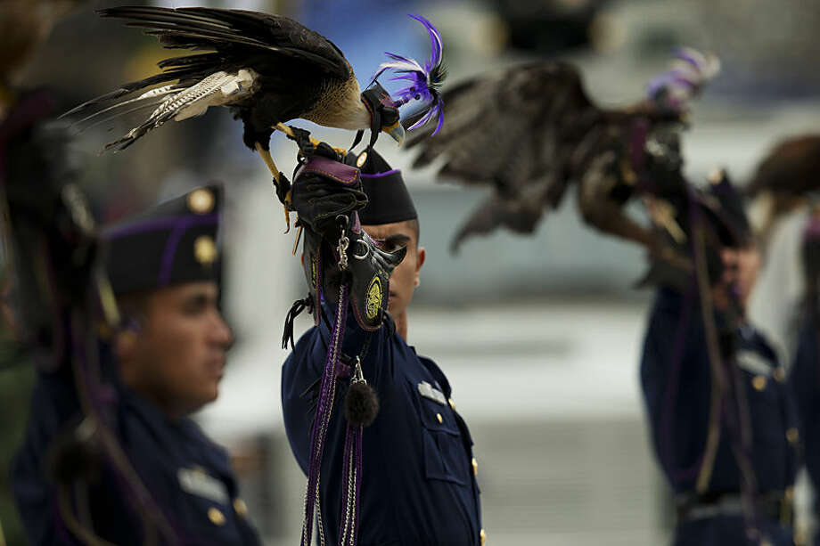 A member of the Air Force carrying a predatory bird looks toward the President as they march past the National Palace during an annual Independence Day parade by Mexico's Armed Forces, in central Mexico City, Mexico, Tuesday, Sept. 16, 2014. Mexico is marking the 204th anniversary of its independence from Spain. (AP Photo/Rebecca Blackwell)