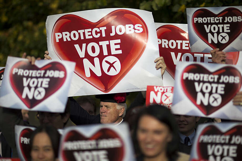 Supporters for the No campaign for the Scottish Independence Referendum hold up banners for the media during a rally in Edinburgh, Scotland, Tuesday, Sept. 16, 2014. The two sides in Scotland's independence debate scrambled Tuesday to convert undecided voters, with just two days to go until a referendum on separation. The pitch of the debate has grown increasingly urgent. Anti-independence campaigners argue that separation could send the economy into a tailspin, while the Yes side accuses its foes of scaremongering. (AP Photo/Matt Dunham)