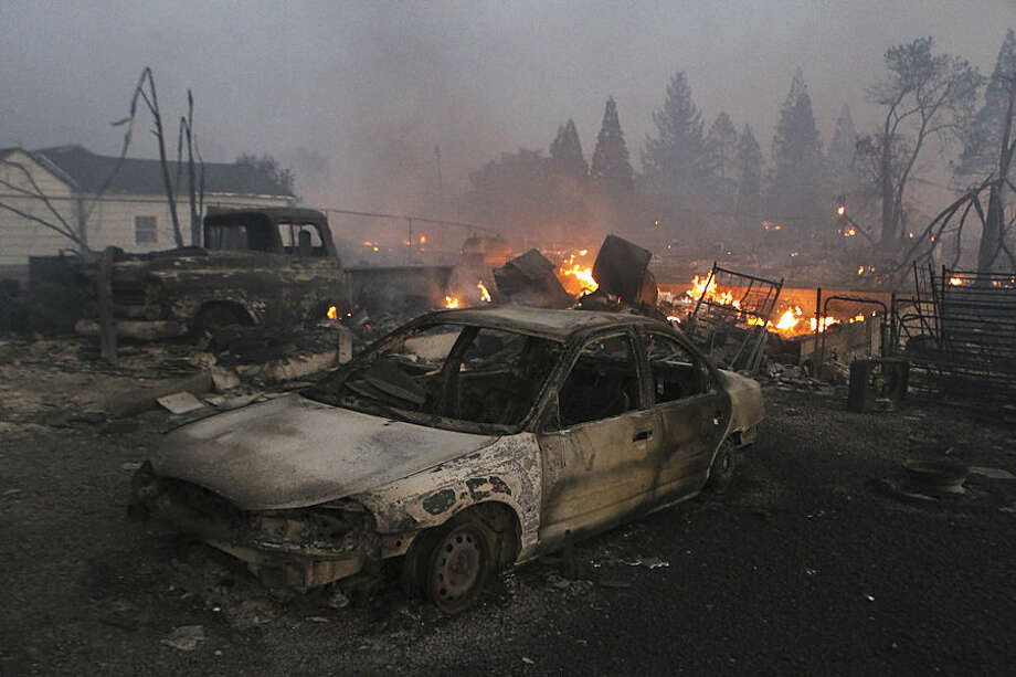 In this Monday, Sept. 15, 2014 photo, vehicles and homes are destroyed in Weed, Calif. where a wind-driven wildfire raced through the hillside neighborhood and forced more than 1,000 people to flee the small town near the Oregon border. The fast-moving blaze, which began Monday, was among nearly a dozen wildfires burning in California that have been exacerbated by the state's third straight year of drought. (AP Photo/The Record Searchlight, Greg Barnette)