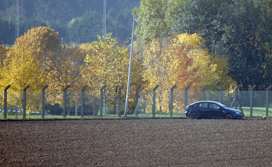 A suspect car, right, is parked in a field outside a military barracks in Flawinne, Belgium on Monday, Oct. 26, 2015. Belgian media are reporting a car has attempted to crash through the gates of an army barracks and that shots have been fired. (AP Photo/Virginia Mayo)