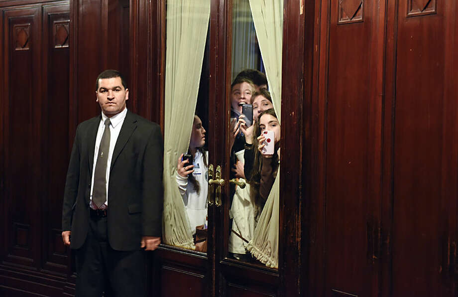Fans of Emma Watson peek from behind a curtain as a security guard stands by inside Parliament in Montevideo, Uruguay, Wednesday, Sept. 17, 2014. Watson is at Parliament in her role as UN Women Goodwill Ambassador for an event organized by women's groups pushing the country's lawmaking body to increase their numbers of elected female senators and deputies. (AP Photo/Matilde Campodonico)