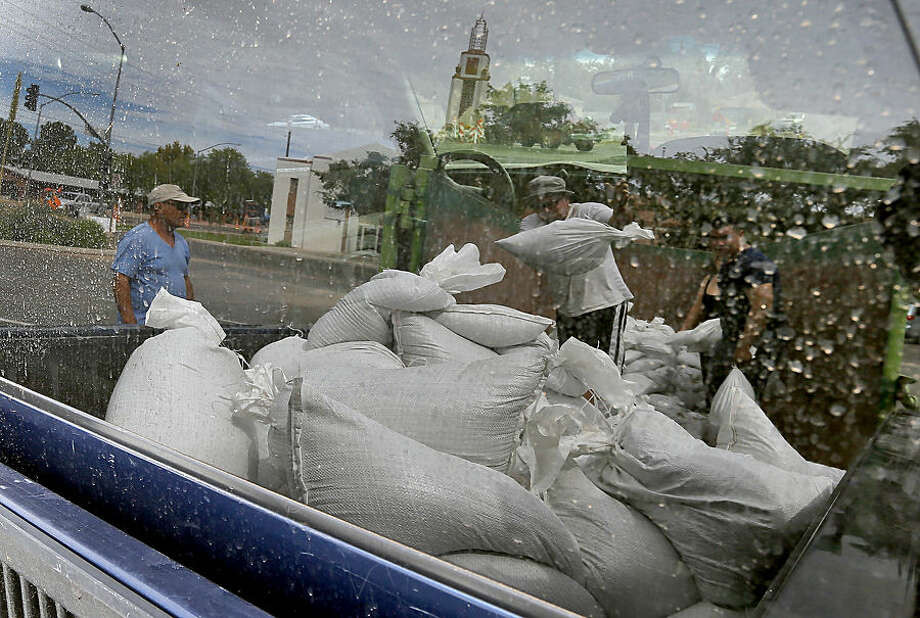 Mesa residents, reflected in a truck window, take free sandbags to protect their homes, Tuesday, Sept. 16, 2014 in Mesa, Ariz. Phoenix area residents are filling sandbags in anticipation for the remnants of Category 3 Hurricane Odille which decimated Mexico's Baja California. (AP Photo/Matt York)