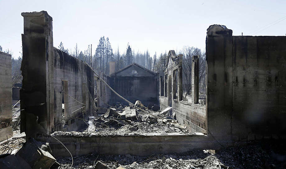 The smoldering empty shell of a local library and a Head Start center are all that remain Tuesday, Sept. 16, 2014, the day after a wildfire swept through Weed, Calif. In just a few hours Monday, wind-driven flames destroyed or damaged roughly 100 homes, a saw mill and a church. (AP Photo/Rich Pedroncelli)