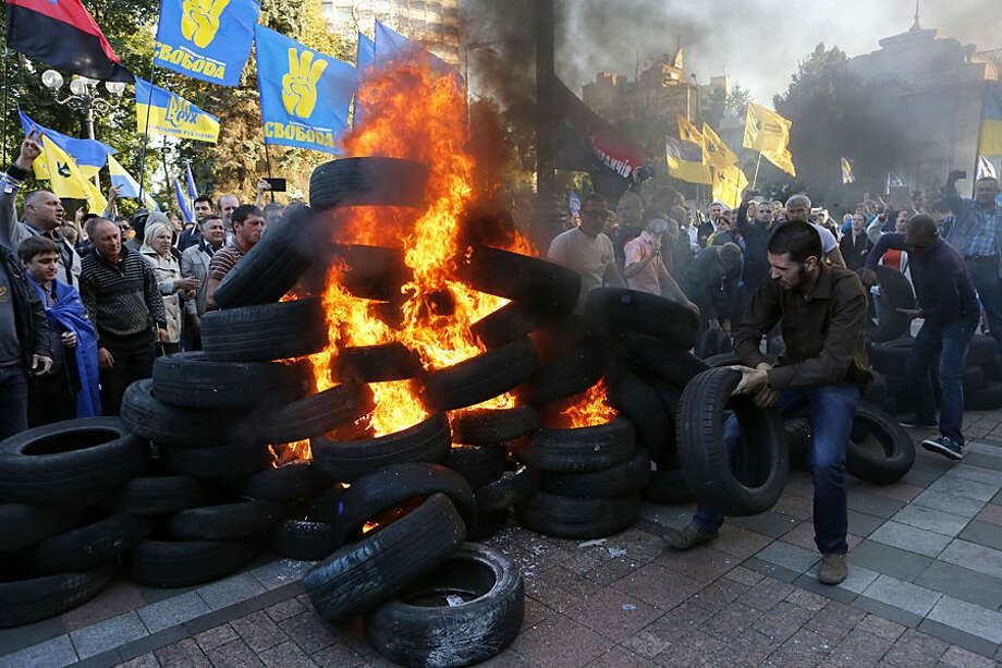 Ukrainian protesters burn tires outside the Ukrainian parliament in Kiev, Ukraine Tuesday, Sept. 16, 2014. The demonstrators rallied in support of a bill that would ban those who cooperated with the old pro-Russian government from running for public office. (AP Photo/Sergei Chuzavkov)