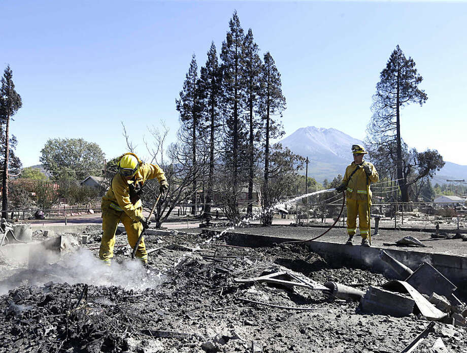 Firefighters hose down a hot spot in the rubble of home Tuesday, Sept. 16, 2014, that was destroyed by a wildfire in Weed, Calif. In just a few hours Monday, wind-driven flames destroyed or damaged roughly 100 homes. (AP Photo/Rich Pedroncelli)