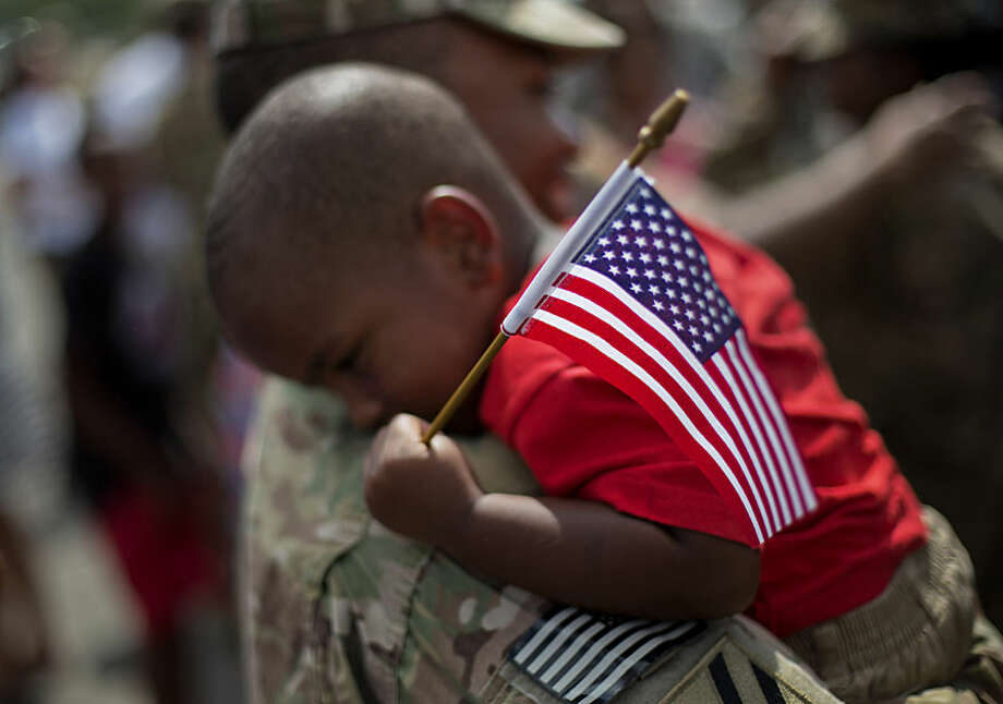 Tyson Hicks, 2, holds an American flag while embraced by his father Sgt. 1st Class Gabriel Hicks upon returning from a deployment to Afghanistan with the Georgia National Guard's 48th Infantry Brigade Combat Team, Tuesday, Sept. 16, 2014, in Macon, Ga. Two hundred Guardsmen returned home Tuesday from a nine-month deployment where they provided security and facilitated the transfers of U.S. military installations to their Afghan counterparts. (AP Photo/David Goldman)