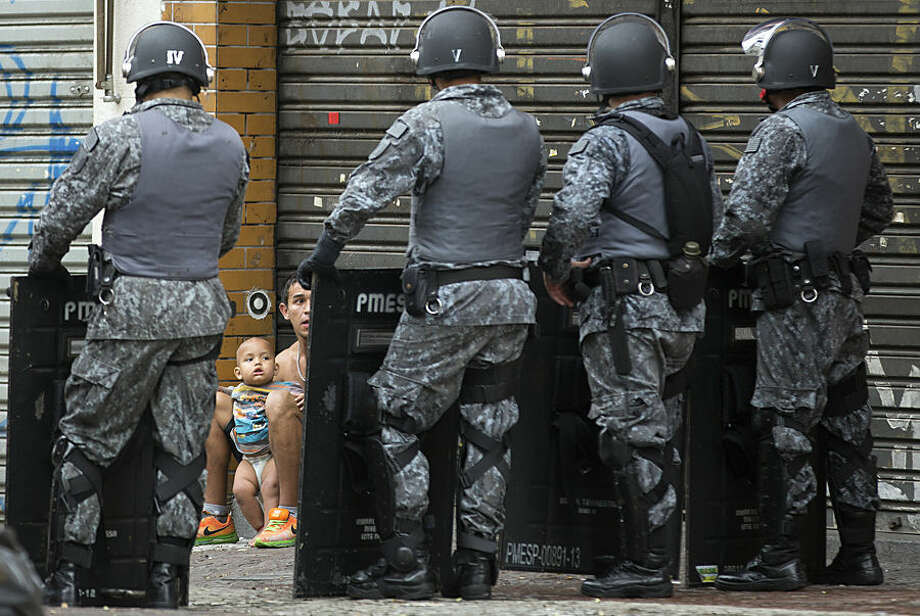 A man and a baby, who voluntarily left an occupied building, are framed by the shields of police standing guard during an eviction operation, in downtown Sao Paulo, Brazil, Tuesday, Sept. 16, 2014. The eviction of 200 families from the building led to violent clashes. Protesters set at least one bus ablaze while police fired rubber bullets, tear gas and stun grenades in an effort to disperse the crowd. (AP Photo/Andre Penner)