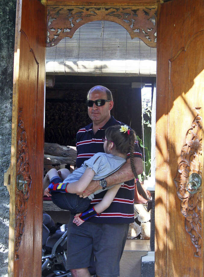 In this June 29, 2015, photo, New Zealander Mark Hooper carries his daughter Charley in Bali, Indonesia. Due to her disability, the Hoopers' decided to give Charley, now 10 years old, a hormone treatment to stop her growth which is considered as a medical miracle by increasing number of parents across the U.S., Europe and New Zealand. Others, on the other hand, see that the very idea of stunting and sterilizing the disabled as a violation of human rights. (AP Photo/Firdia Lisnawati)