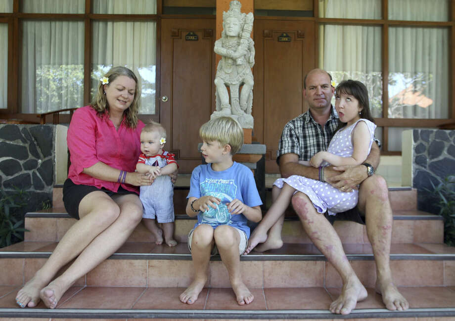 In this Aug. 12, 2015 photo, Jenn, left, and Mark Hooper sit for a photo with their three children, from left, Cody, Zak and Charley in Bali, Indonesia. Mark quit his job as an architectural draftsman to help Jenn with the kids. They get by on a government-funded insurance program that supports at-home caregivers, and sales of a torso support wrap Jenn designed for disabled children. (AP Photo/Firdia Lisnawati)