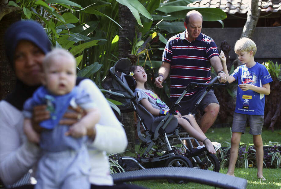 In this June 29, 2015 photo, New Zealander Mark Hooper, center, plays with his daughter, Charley, and son Zak, right, as his youngest son Cody, left, is carried by a nanny in Bali, Indonesia. The Hoopers' fight to get her the hormone treatment known as growth attenuation was grueling. Although an increasing number of parents across the U.S., Europe and New Zealand consider it a medical miracle, others see the very idea of stunting and sterilizing the disabled as a violation of human rights. (AP Photo/Firdia Lisnawati)