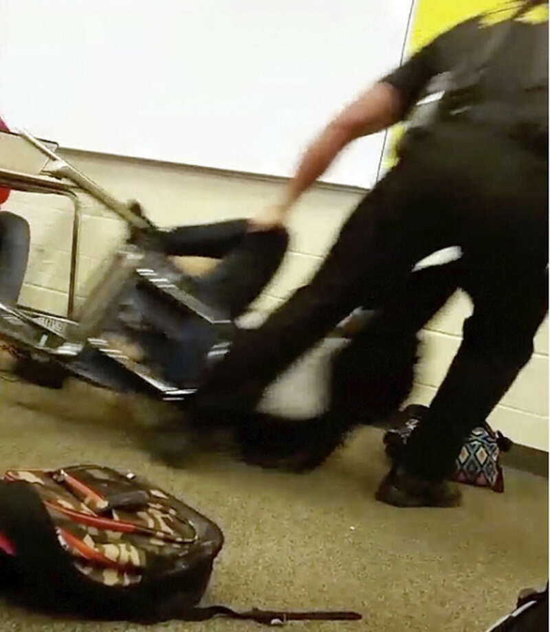In this Monday, Oct. 26, 2015 photo made from video taken by a Spring Valley High School student, Senior Deputy Ben Fields drags a student across the floor as he removes her from her chair after she refused to leave her high school math class, in Columbia S.C. The Justice Department opened a civil rights investigation Tuesday after Fields flipped the student backward in her desk and tossed her across the floor. (AP Photo)