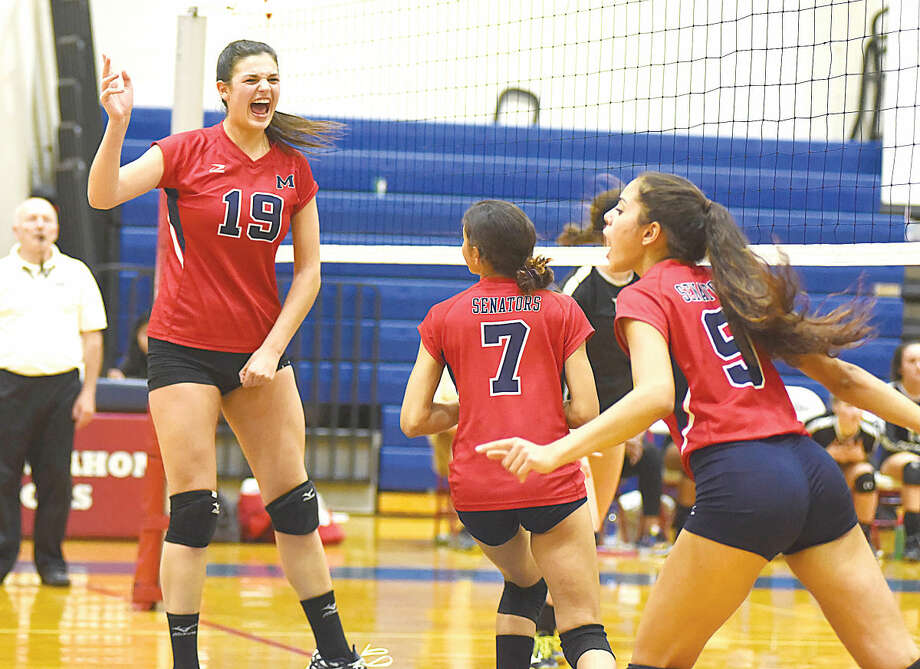Hour photo/John Nash - Brien McMahon volleyball players Meredith Pellegrino (19), Elizabeth Wimpfheimer (7) and Deborah Wimpfheimer celebrate a point during the Senators' 3-0 win over Trumbull on Tuesday night.