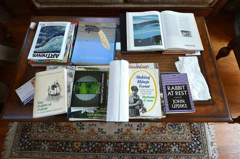 A coffee table covered in art books and a roll of paper towels in paper towel artist Ken Delmar's Stamford home.