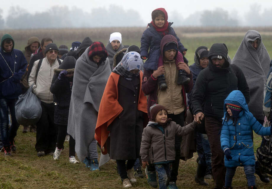 Migrants move through a field after crossing from Croatia, in Rigonce, Slovenia, Sunday, Oct. 25, 2015. Thousands of people are trying to reach central and northern Europe via the Balkans, but often have to wait for days in mud and rain at the Serbian, Croatian and Slovenian borders. (AP Photo/Darko Bandic)