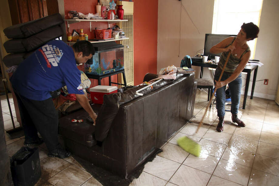 Elena Santellan sweeps water while Pedro Hernandez moves a sofa in El Paso, Texas, Thursday, Sept. 18, 2014. Heavy rains caused street flooding and other incidents in Far West Texas and Southeastern New Mexico. (AP Photo/Juan Carlos Llorca)