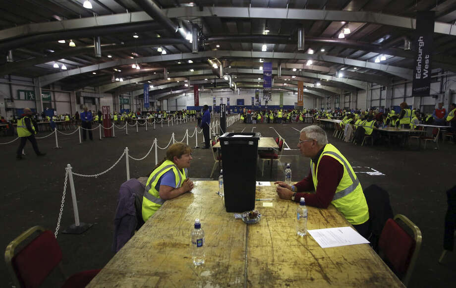 Officials wait for ballot boxes to be opened as counting begins in the Scottish Independence Referendum at the Royal Highland Centre in Edinburgh, Scotland, Thursday Sept. 18, 2014. As the polls closed Thursday and vote-counting began, there was a quiet thrill of history in the making on the fog-shrouded streets of Scotland's capital, Edinburgh. Many Scots were staying up all night in homes and bars to watch the results roll in. (AP Photo/David Cheskin)