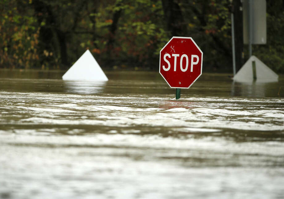 A stop sign stands almost completely submerged after heavy rains on a roadway into White Rock Lake Friday, Oct. 23, 2015, in Dallas. Residents braced for more rain this weekend from other storms that could spin off from massive Hurricane Patricia approaching southwest Mexico. (AP Photo/Tony Gutierrez)