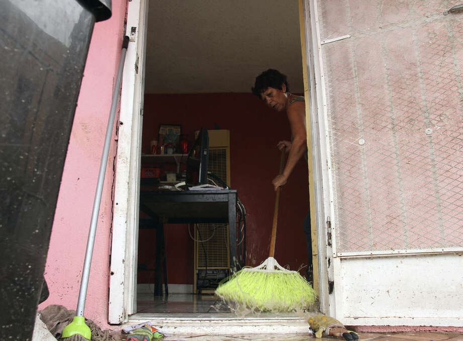 Elena Santellan sweeps water from Pedro Hernandez's home in El Paso, Texas, Thursday, Sept. 18, 2014. Heavy rains caused street flooding and other incidents in Far West Texas and Southeastern New Mexico. (AP Photo/Juan Carlos Llorca)