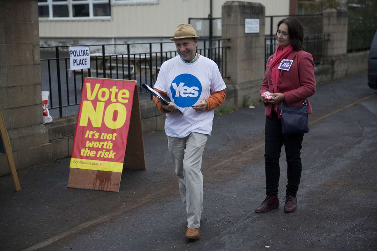 A Yes campaigner and a No campaigner stand outside a polling place in Edinburgh, Scotland, Thursday, Sept. 18, 2014. Polls have opened across Scotland in a referendum that will decide whether the country leaves its 307-year-old union with England and becomes an independent state. (AP Photo/Matt Dunham)