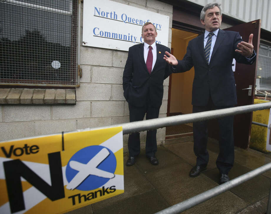 Britain's former Prime Minister Gordon Brown gestures outside the polling station at North Queensferry Community Centre, in Queensferry, Scotland. Polls opened across Scotland in a referendum that will decide whether the country leaves its 307-year-old union with England and becomes an independent state. (AP Photo//PA, Andrew Milligan) UNITED KINGDOM OUT NO SALES NO ARCHIVE