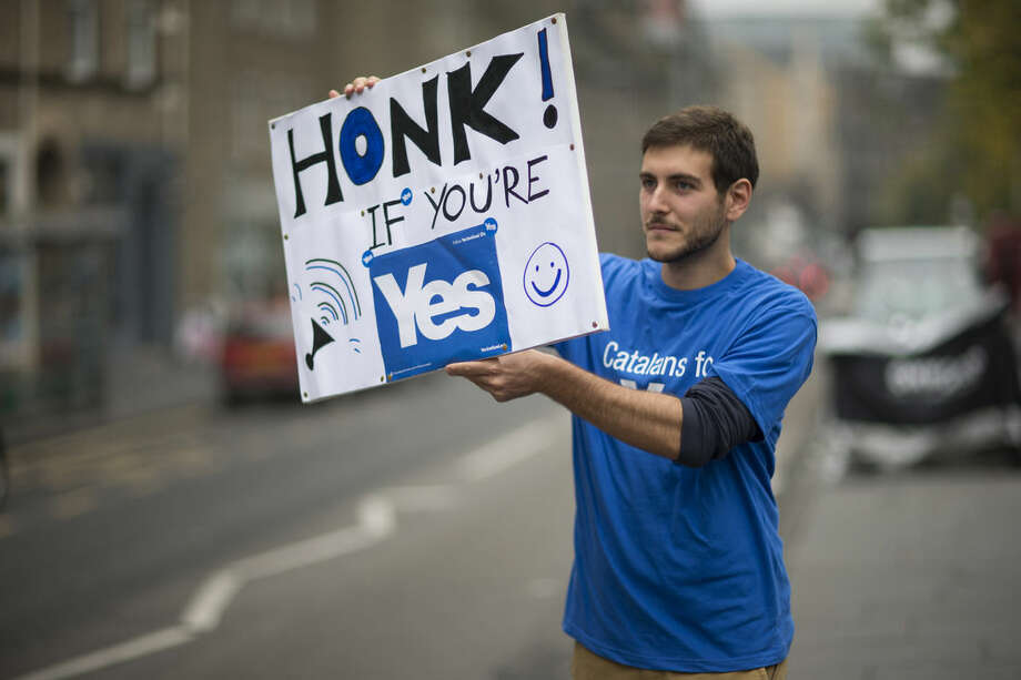 David Aguilar from Catalonia, who is visiting Scotland to support the Scottish independence referendum, holds up a placard supporting a Yes vote at passing motorists in Edinburgh, Scotland, Thursday, Sept. 18, 2014. Polls have opened across Scotland in a referendum that will decide whether the country leaves its 307-year-old union with England and becomes an independent state. (AP Photo/Matt Dunham)