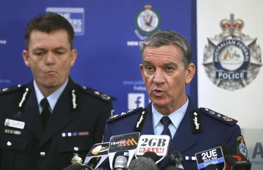 New South Wales Police Commissioner Andrew Scipione, right, and Australian Federal Police Acting Commissioner Andrew Colvin describe how 800 federal and state police officers raided more than two dozen properties as part of the operation in Sydney, Thursday, Sept. 18, 2014. Australian police detained 15 people earlier on Thursday in a major counterterrorism operation, saying intelligence indicated a random, violent attack was being planned on Australian soil. (AP Photo/Rick Rycroft)