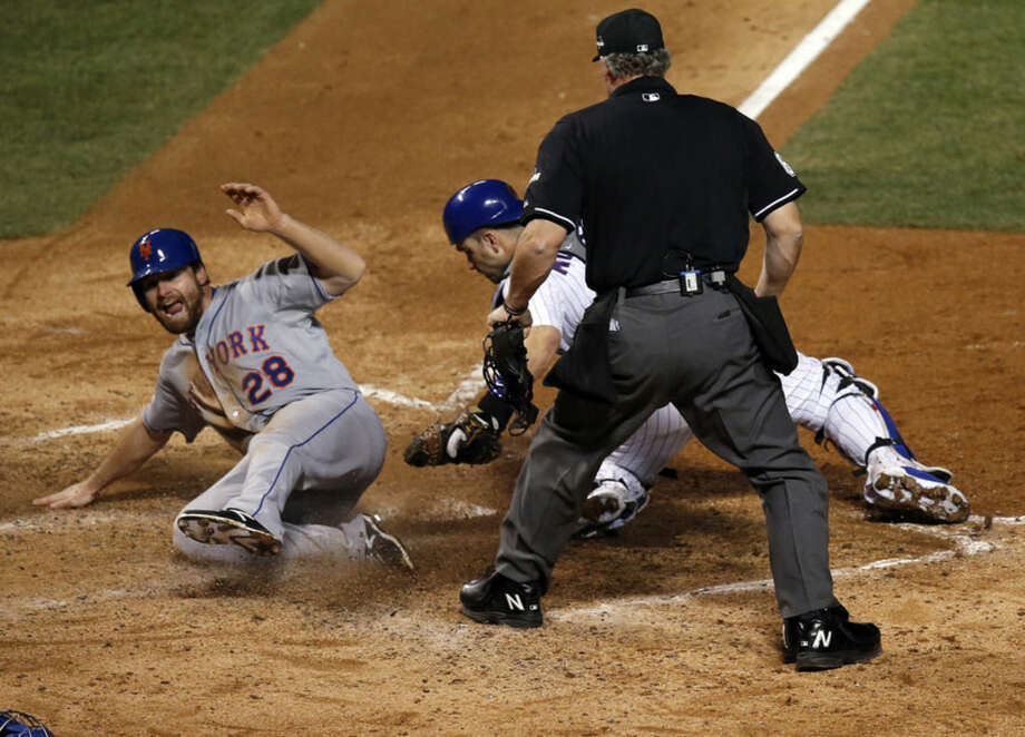 New York Mets' Daniel Murphy scores past Chicago Cubs catcher Miguel Montero during the seventh inning of Game 3 of the National League baseball championship series Tuesday, Oct. 20, 2015, in Chicago. Murphy scored from third on a ball hit by Lucas Duda. (AP Photo/Charles Rex Arbogast)