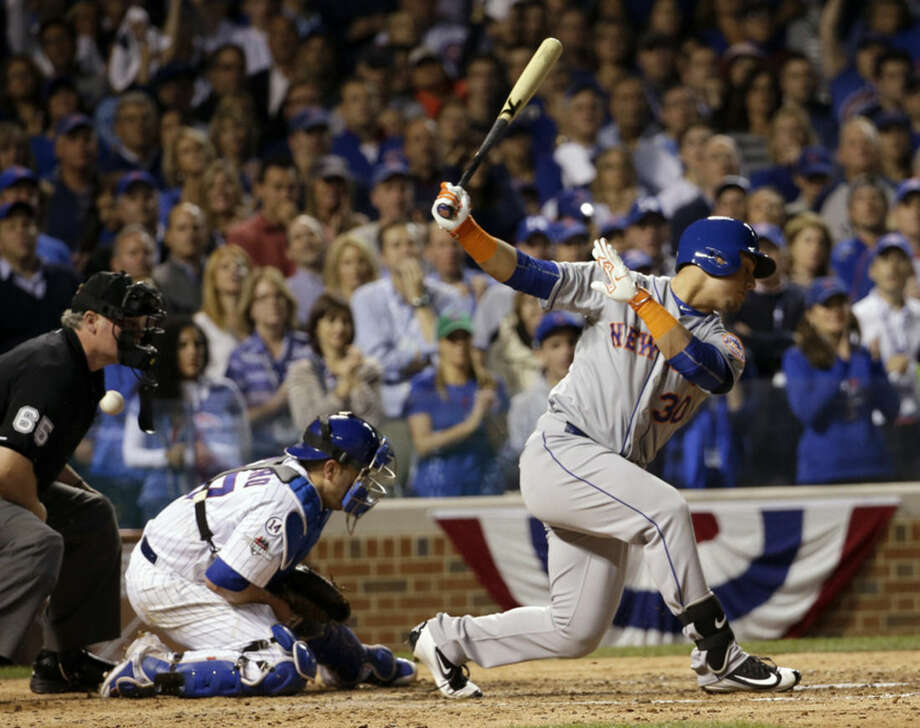 Chicago Cubs catcher Miguel Montero can't handle a pitch as New York Mets' Michael Conforto bats during the sixth inning of Game 3 of the National League baseball championship series Tuesday, Oct. 20, 2015, in Chicago. Yoenis Cespedes scored from third on the play. (AP Photo/David J. Phillip)