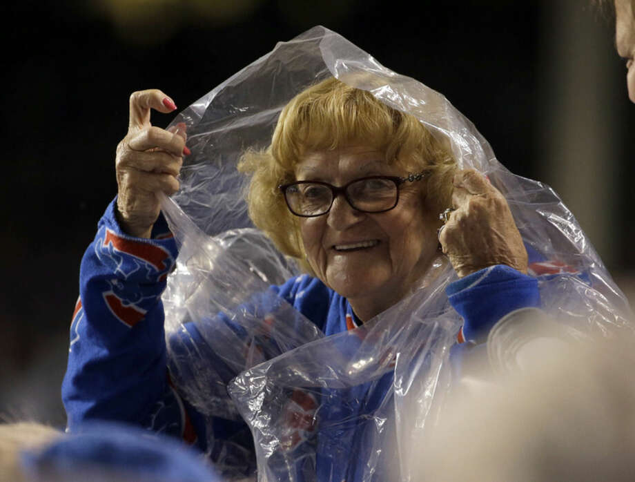 A fan gets ready for some rain during the seventh inning of Game 3 of the National League baseball championship series between the New York Mets and the Chicago Cubs Tuesday, Oct. 20, 2015, in Chicago. (AP Photo/Nam Y. Huh)