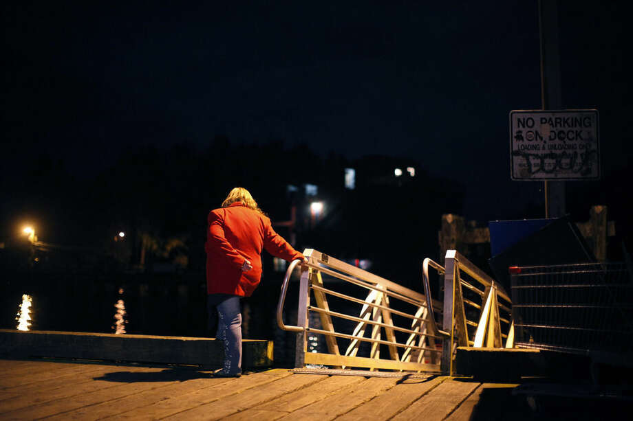 A woman pays her condolences from the First St. dock to passengers of a capsized whale watching boat in Tofino, west coast of Vancouver, Canada, early Monday, Oct. 26, 2015. The whale watching boat with 27 people on board sank off Vancouver Island on Sunday, Canadian authorities said. (Chad Hipolit/The Canadian Press via AP)