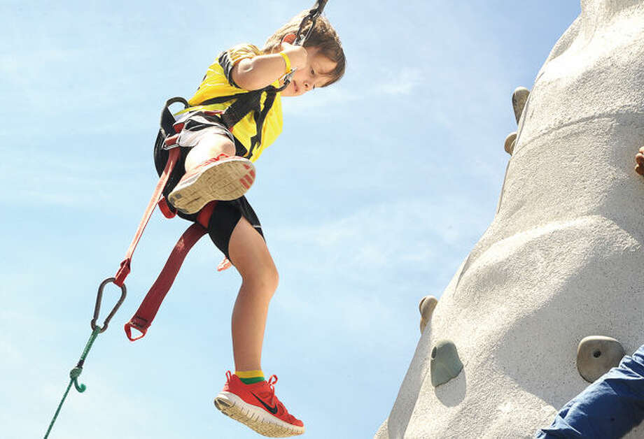 Freddy Friedman 7 scales the rock wall Sunday at the Wilton Rotary Carnival. Photo/Matthew Vinci