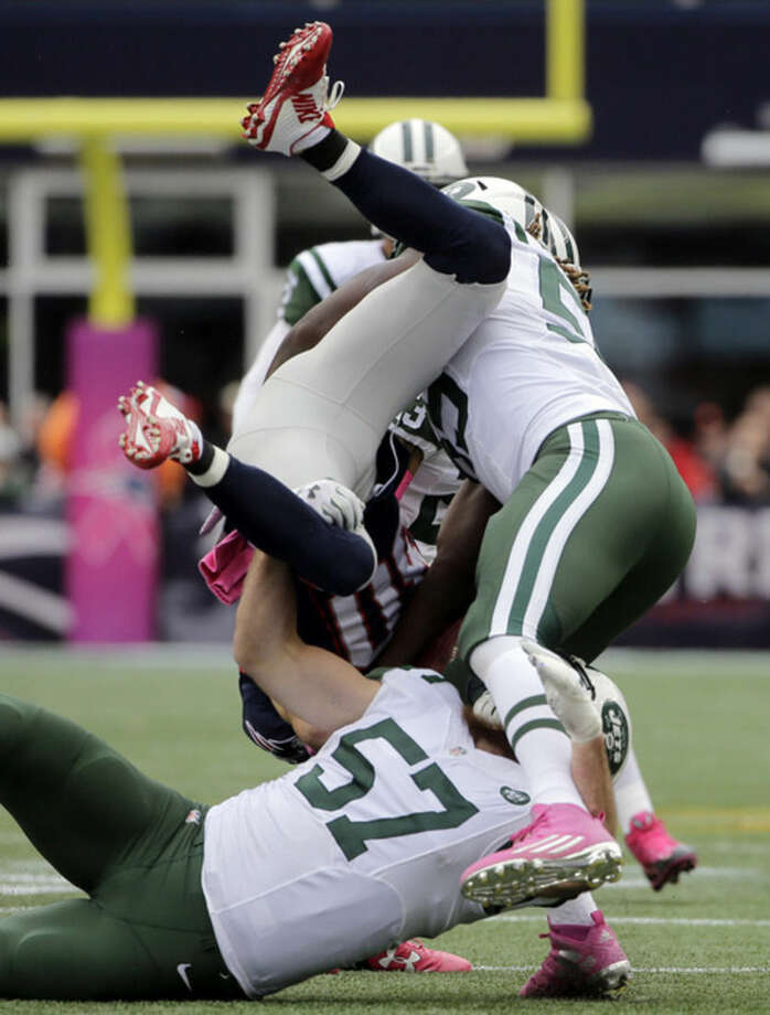 New York Jets linebackers Lorenzo Mauldin, right, and Trevor Reilly (57) upend New England Patriots wide receiver Danny Amendola (80) during the second half of an NFL football game, Sunday, Oct. 25, 2015, in Foxborough, Mass. (AP Photo/Steven Senne)