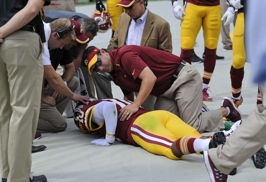Washington Redskins quarterback Robert Griffin III (10) is attended to on the sideline after injuring his left ankle during the first half of an NFL football game against the Jacksonville Jaguars, Sunday, Sept. 14, 2014, in Landover, Md. (AP Photo/Nick Wass)