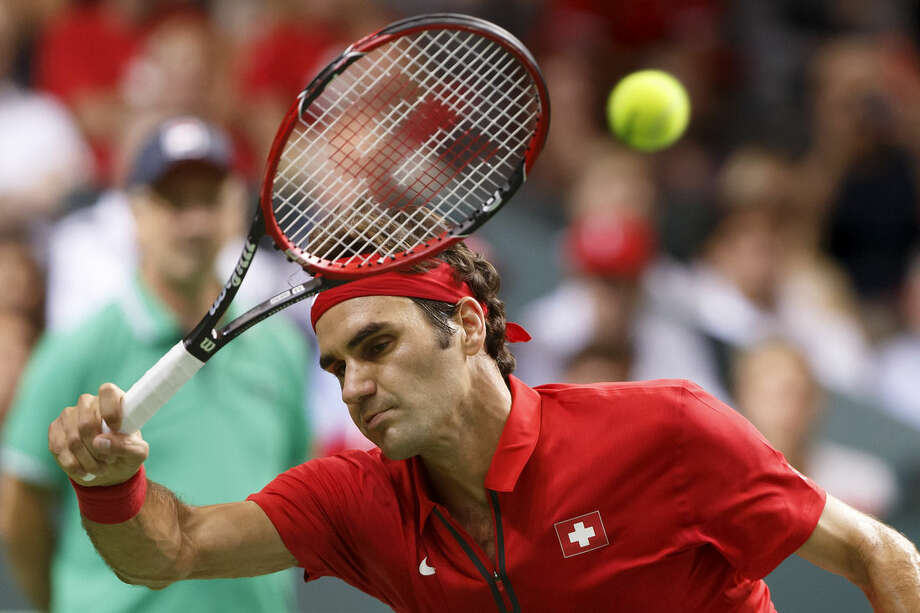 Roger Federer, of Switzerland, returns a ball to Fabio Fognini, of Italy, during the third single match of the tennis Davis Cup World Group semifinal between Switzerland and Italy, in Geneva, Switzerland, Sunday, Sept. 14, 2014. (AP Photo/Keystone,Salvatore Di Nolfi)