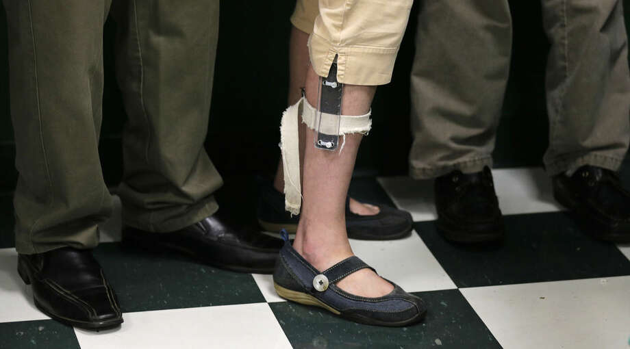 In this Aug. 13, 2014, photo, a female student wearing a shocking device on her leg, lines up with classmates after lunch at the Judge Rotenberg Educational Center in Canton, Mass. Many students at the school, who were born with Autism and development disorders, wear shocking devices to control violent outbreaks. The Food and Drug Administration is considering whether to ban the devices used at the center, the only place in the country known to use electrical shocks as aversive conditioning for aggressive students. (AP Photo/Charles Krupa)