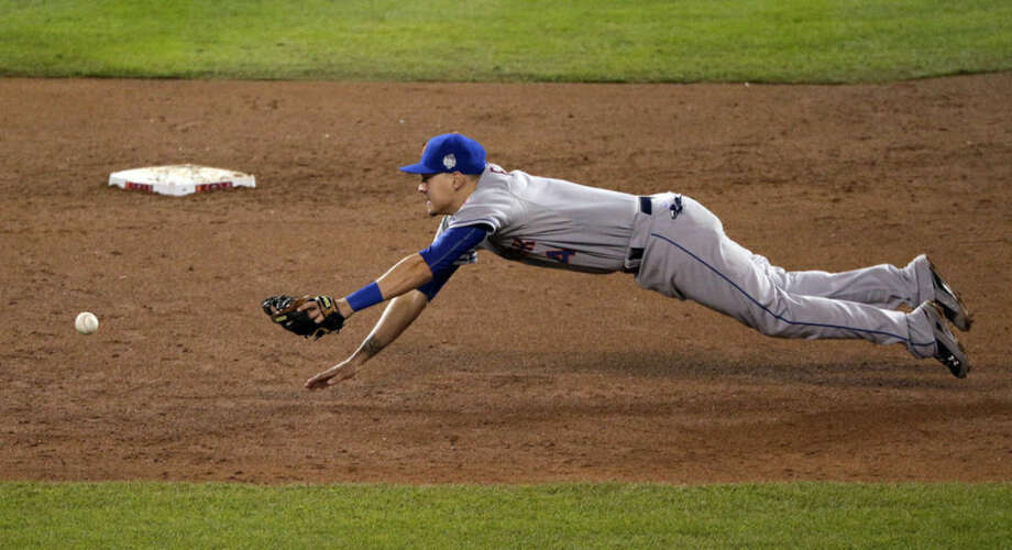 New York Mets shortstop Wilmer Flores dives for a Kansas City Royals' Eric Hosmer two-RBI single during the fifth inning of Game 2 of the Major League Baseball World Series Wednesday, Oct. 28, 2015, in Kansas City, Mo. (AP Photo/Charlie Riedel)