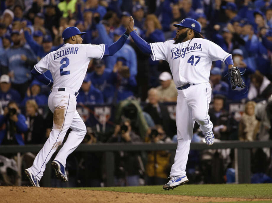Kansas City Royals pitcher Johnny Cueto (47) celebrates with Alcides Escobar after a ground ended the seventh inning of Game 2 of the Major League Baseball World Series against the New York Mets Wednesday, Oct. 28, 2015, in Kansas City, Mo. (AP Photo/Matt Slocum)